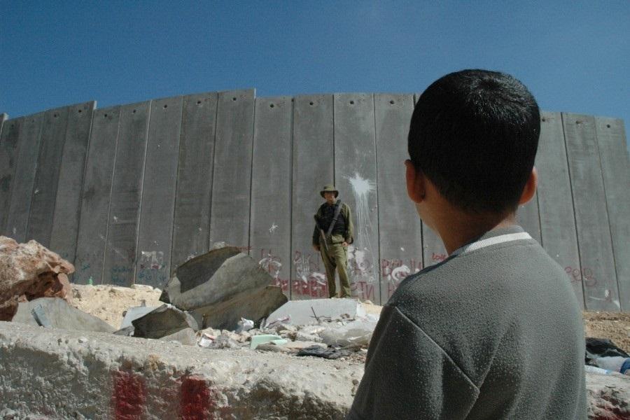 Palestinski dječak i izraelski vojnik ispred zida na okupiranoj Zapadnoj obali (izvor: commons.wikimedia.org).