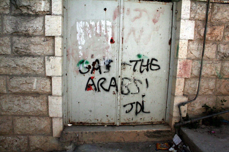 Grafit izraelskih kolonista na vratima palestinske kuće u Hebronu, potpisan akronimom JDL, tzv. Židovske obrambene lige (izvor: commons.wikimedia.org).