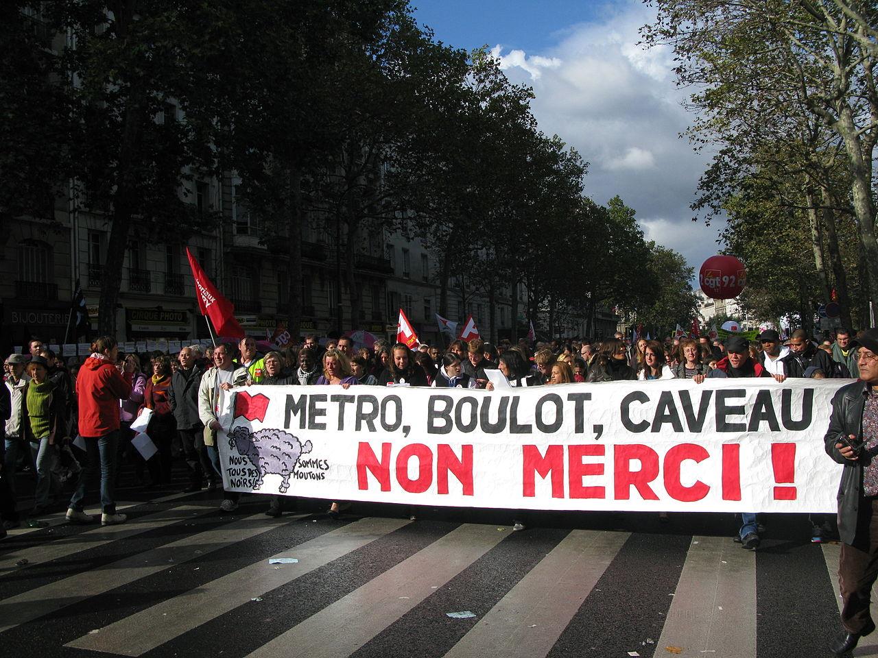 """Prosvjedi na ulicama Pariza protiv mirovinske reforme iz 2010. godine; na transparentu piše: """"Metro, posao, groblje - Ne hvala!"""" (izvor: commons.wikimedia.org)."""