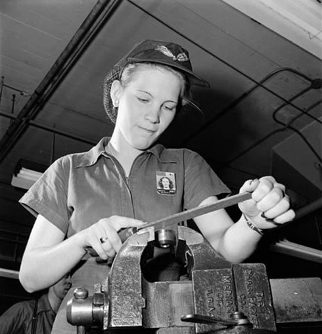 Radnica u tvornici turpijom uklanja višak materijala s komponente dok sa razglasa trešti glazba, Kanada 1943. godine (izvor: BiblioArchives / LibraryArchives prema Creative Commons licenci).