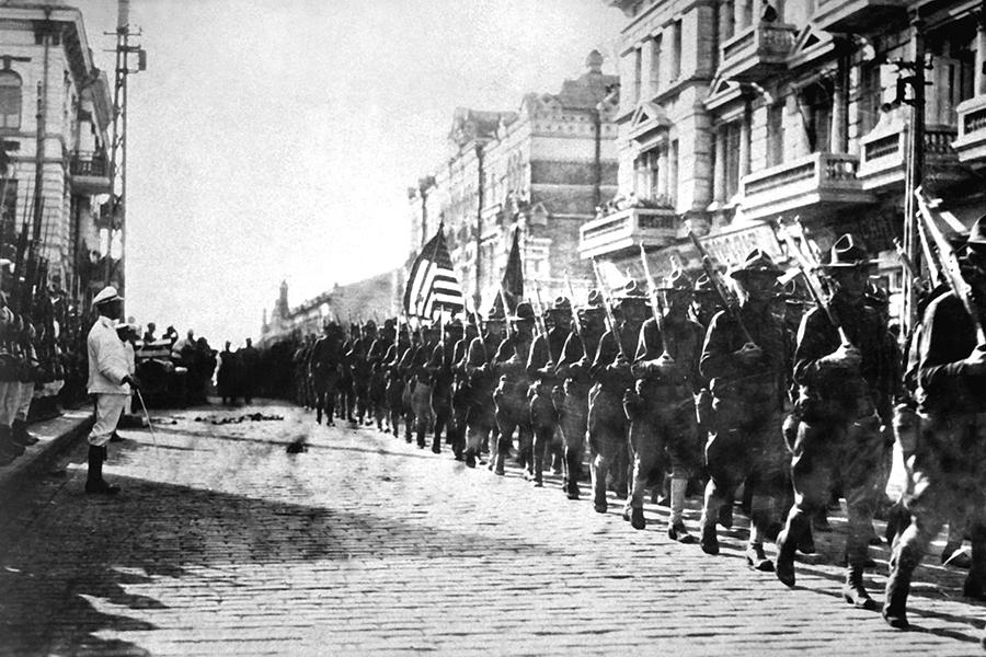 Američke trupe paradiraju Vladivostokom ispred zgrade koju su zauzeli pripadnici Čehoslovačke legije, pored postrojenih japanskih marinaca, Sibir, kolovoz, 1918. (izvor: Wikipedia.org)